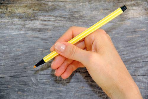 Werbetexter Monika Weber von monswap solutions hält einen gelben Stift schreibbereit in der Hand.