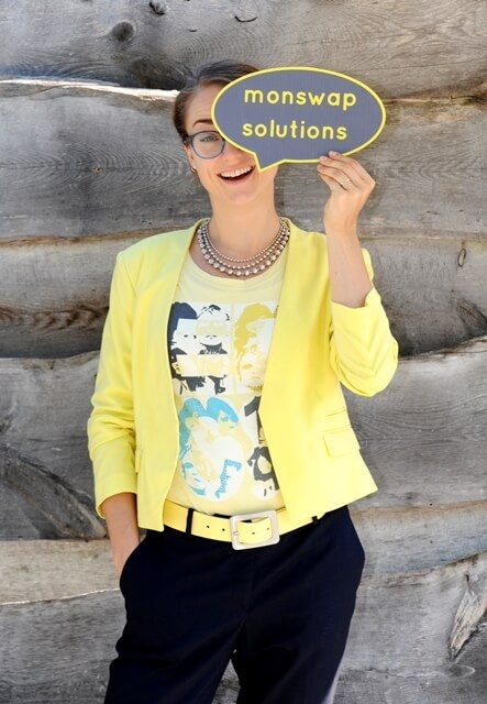 Monika Weber von monswap solutions, freie Texterin in München, Augsburg und weltweit, hält sich ihr Logo, eine Sprechblase, vors Gesicht.