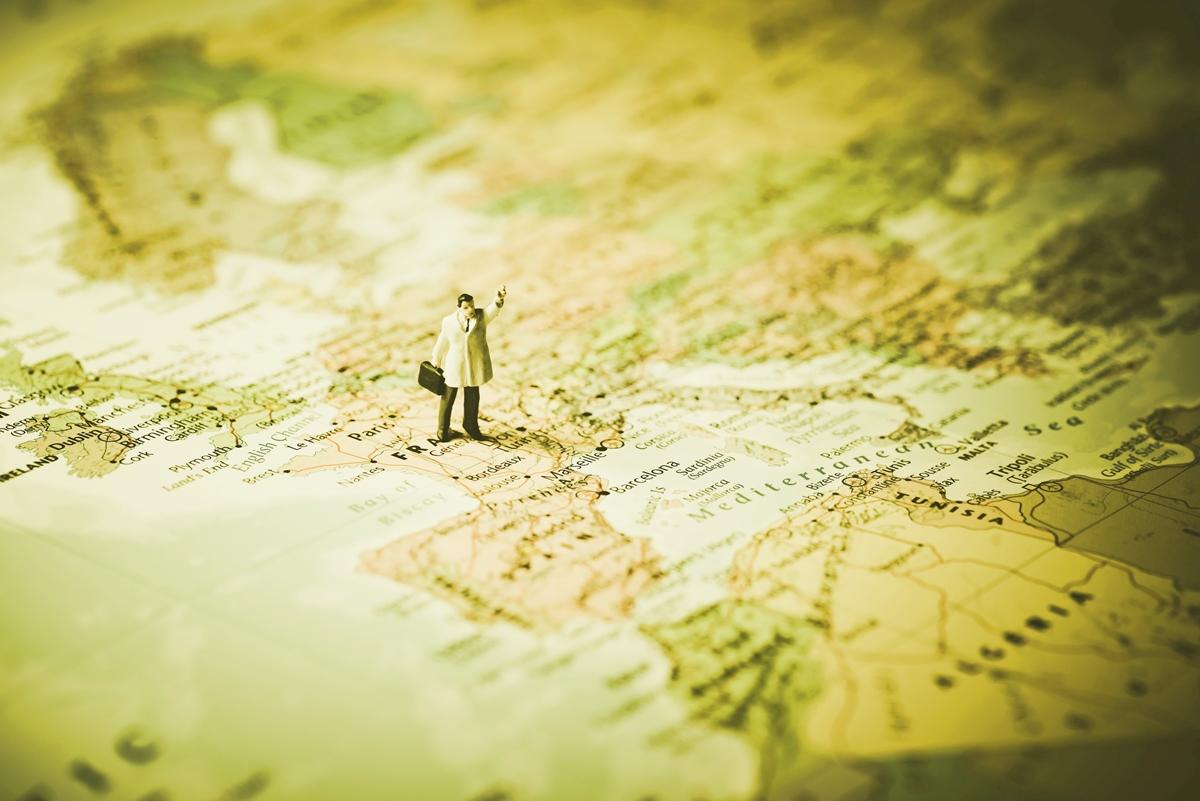 Symbolbild Mehrsprachige SEO international: Plastikfigur eines Geschäftsmanns steht auf einer Weltkarte