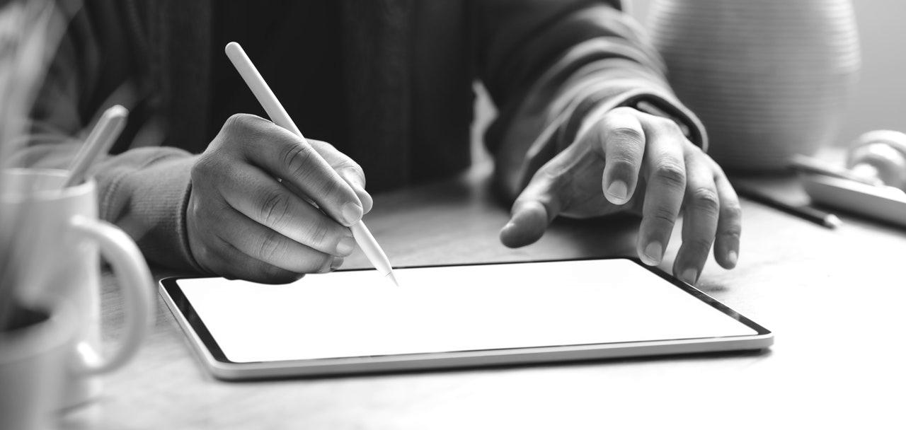 Symbolbild Newsletter schreiben: Hand schreibt mit Touchpen auf ein Tablet