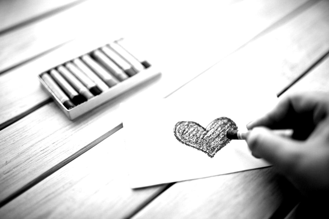 Symbolbild Newsletter Texter: Hand malt Herz auf ein Papier