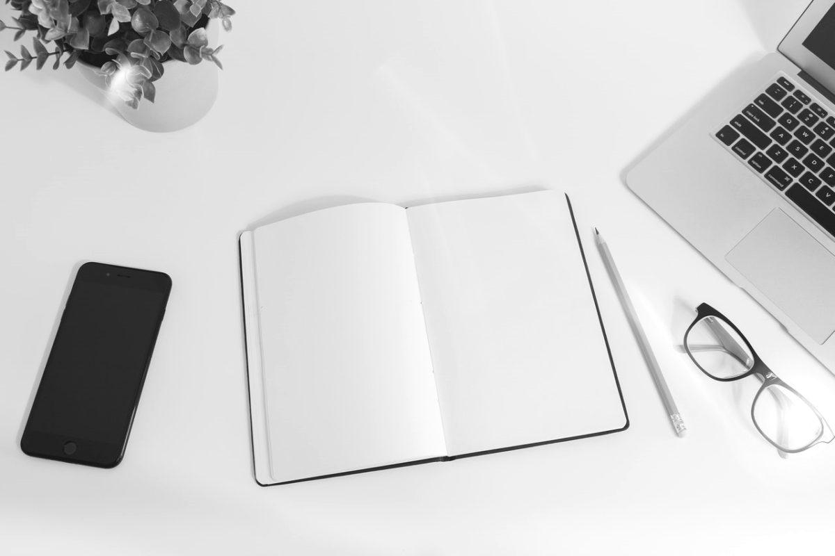 Symbolbild Professionelle Texte schreiben lassen: aufgeschlagenes Notizbuch mit Stift