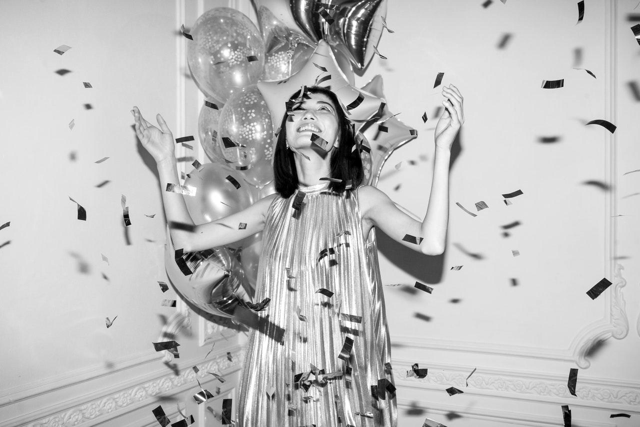 Symbolbild für Search Intent Optimization: Glückliche Frau mit Konfetti und Ballons
