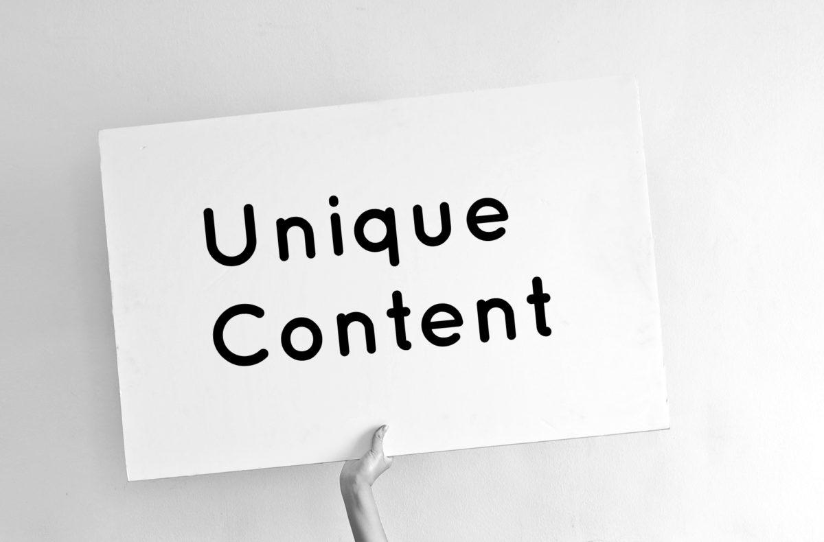 Symbolbild für Unique Content kaufen: Hand hält Schild mit Unique Content
