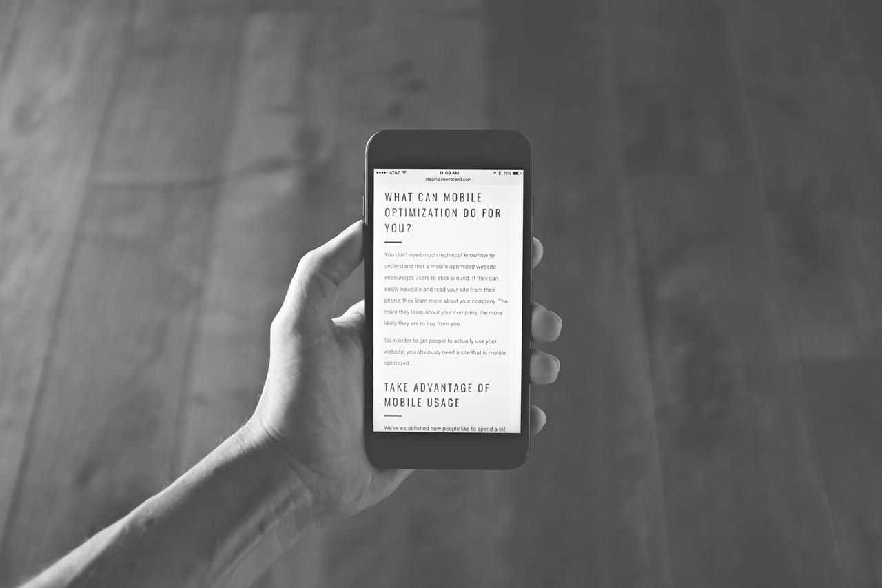 Symbolbild für Was bedeutet SEO: Hand hält Smartphone mit einem Text über mobile Suchmaschinenoptimierung